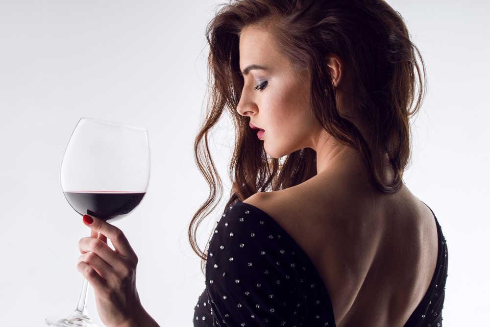 Copa de vino en mano, mujer elegante en la ficción